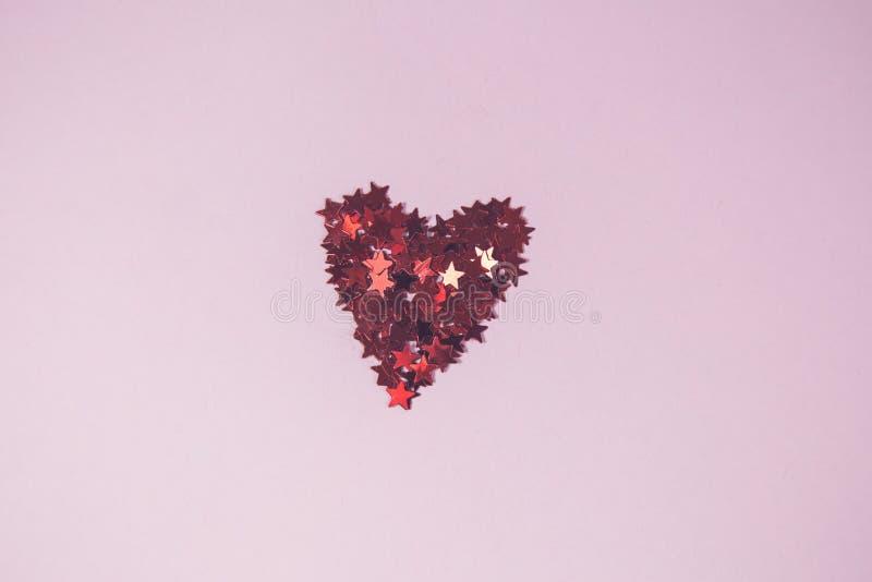 Hjärta som göras av röda konfettier i form av stjärnan, på rosa bakgrund royaltyfri bild