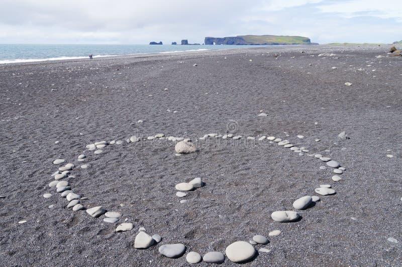 Hjärta som göras av små stenar på sand, på stranden fotografering för bildbyråer