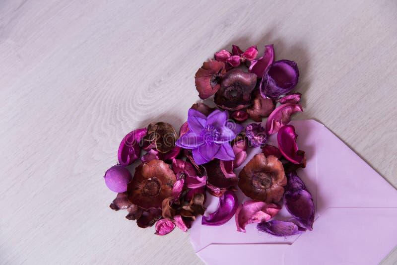 Hjärta som göras från purpurfärgade torkade blommor och kronblad i det lila kuvertet, blom- lekmanna- sammansättningslägenhet, bä arkivbild