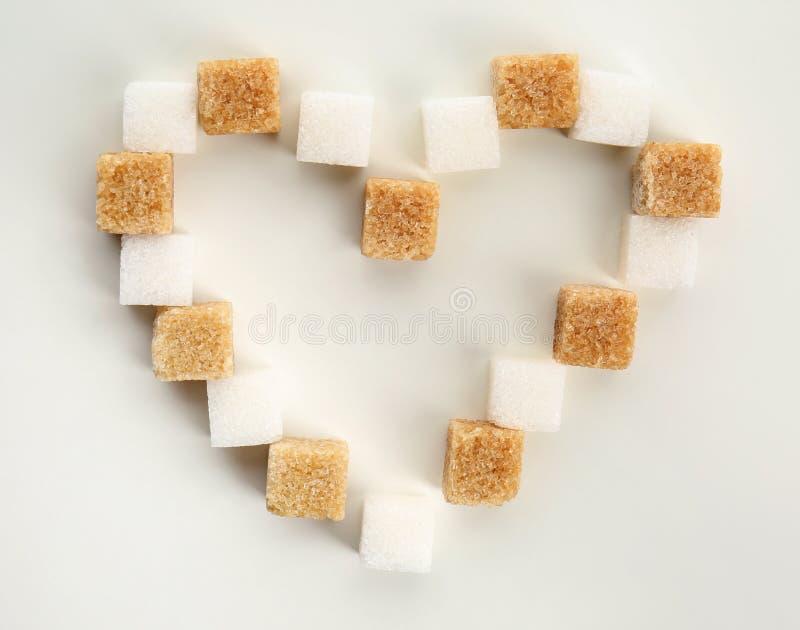 Hjärta som göras med olika kuber av socker på vit bakgrund royaltyfria bilder