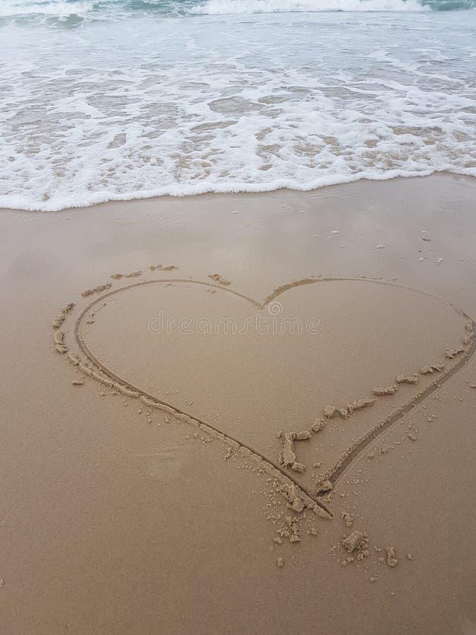 Hjärta som målas på sand med skummande vågor som rusar in mot den arkivfoton