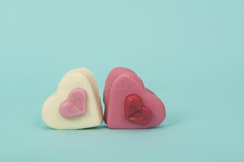 Hjärta två sheaped rosa petit ` s för fyra godis på en turkosbackgro royaltyfri fotografi