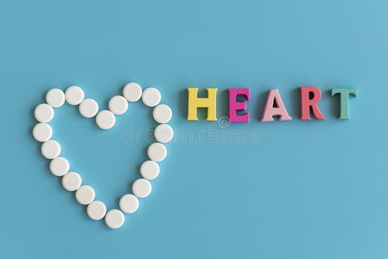 Hjärtabegrepp på en blå bakgrund Hjärta av vita preventivpillerar på en blå bakgrund Hjärtainskrift arkivfoton