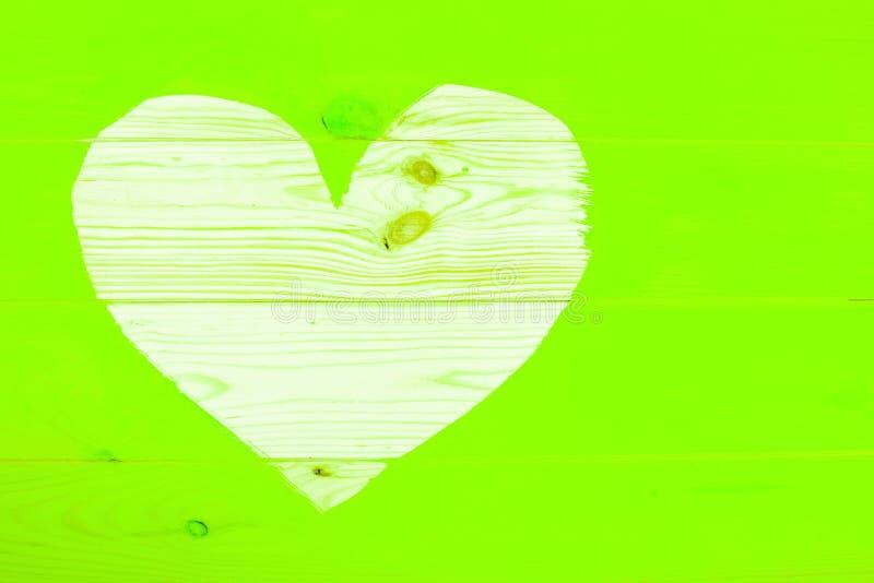 Hjärtaform av naturlig träbakgrund som omger målad ufo-gräsplanyttersida royaltyfri foto
