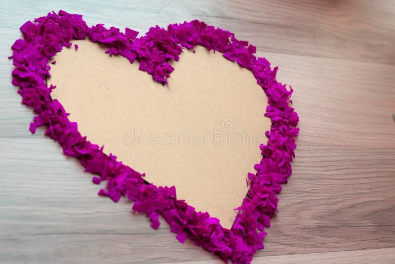 Hjärtaform av purpurfärgade konfettier - rosa färger kopierar utrymme och bakgrund arkivfoton