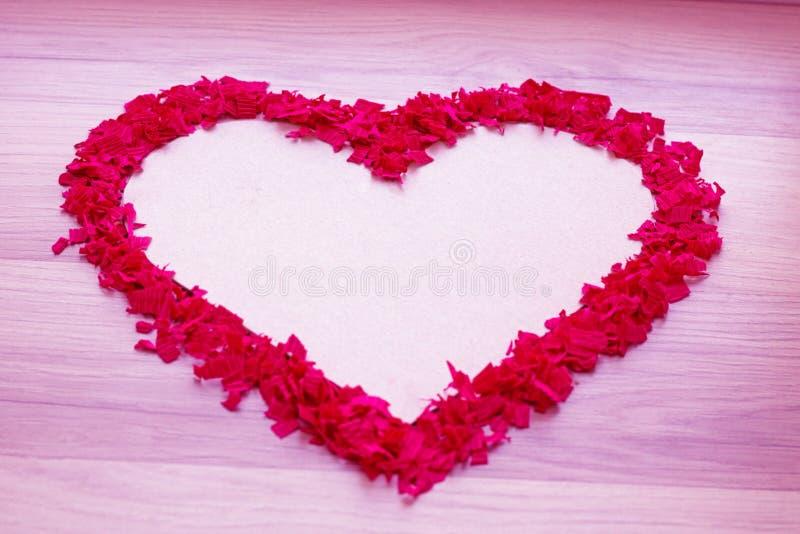 Hjärtaform av röda konfettier - vit kopieringsutrymme och rosa färgbakgrund royaltyfri foto