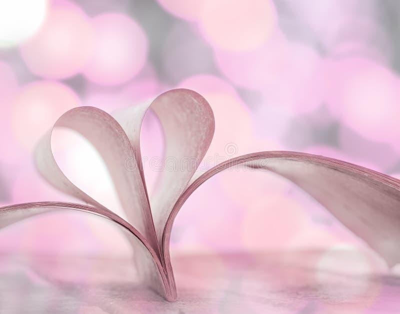 Hjärtaform från öppnade boksidor med bokehbakgrund arkivbild