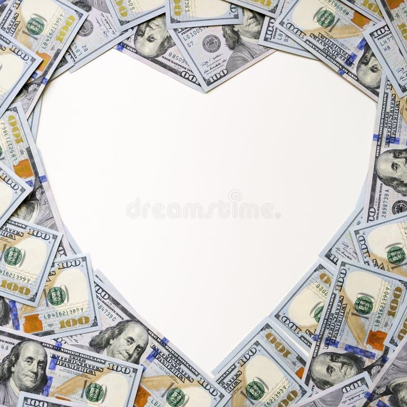 Hjärtaform gjorde av hundra dollarräkningar på vit bakgrund Utrymme f?r text Hög av usd, amerikanska kassapengar royaltyfri foto
