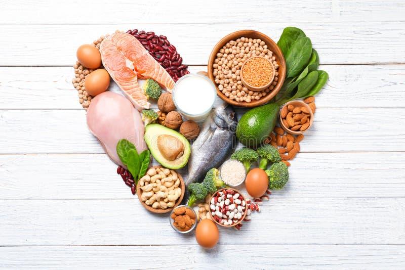 Hjärtaform gjorde av naturlig mat högt i protein på vit träbakgrund royaltyfri fotografi