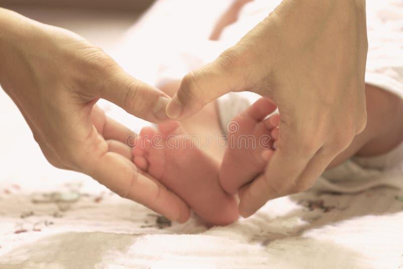 Hjärtaform med de nyfödda benen för förälskelse- och omsorgbegrepp royaltyfri foto
