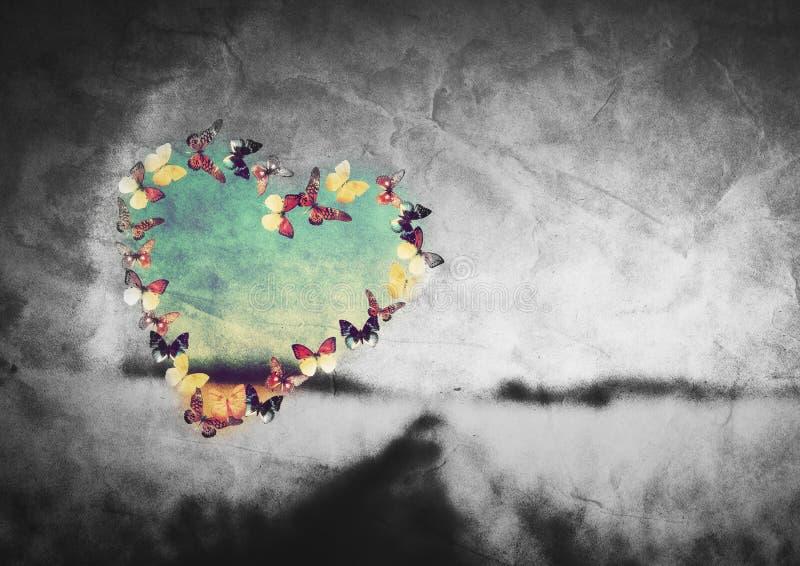Hjärtaform som göras av färgrika fjärilar på svartvitt fält royaltyfria bilder