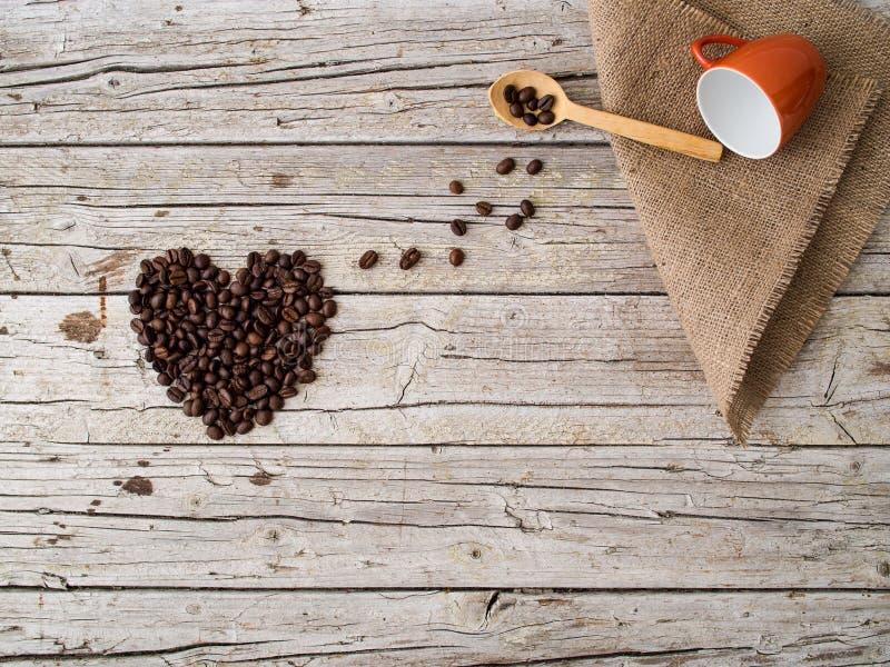 Hjärtaform som göras av kaffebönor, träskeden och koppen på trä arkivbild
