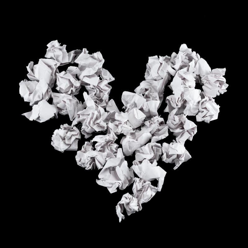 Hjärtaform som göras av skrynkliga pappers- bollar arkivbilder