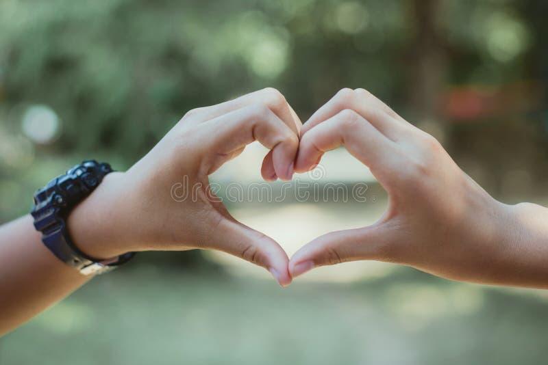 Hjärtaform som göras med händer av den kvinnliga studenten, förälskelsesymbolconce royaltyfria bilder