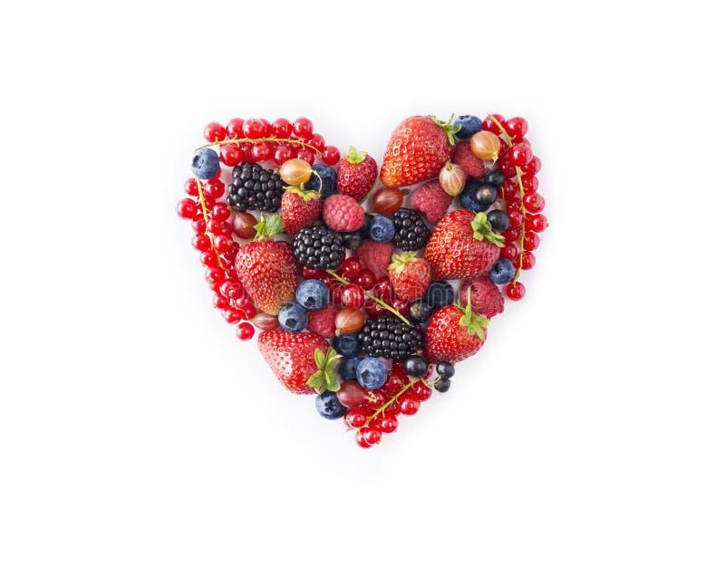Hjärtaform sorterade bärfrukter på vit bakgrund Svart-blått och röd mat Mogna blåbär, röda vinbär, hallon, sugrör royaltyfri bild