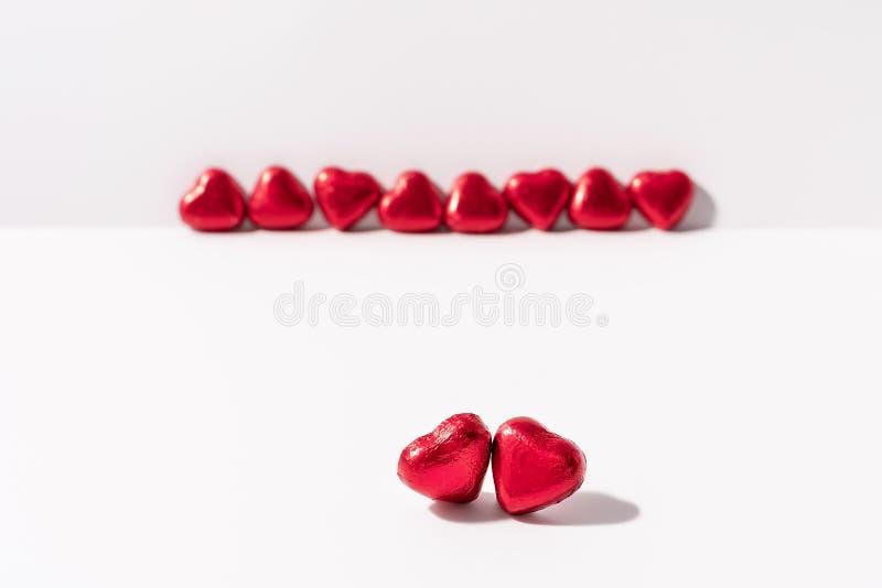 Hjärtaformchoklader som slås in i röd folie på vit bakgrund Bukett av rosor i bakgrunden Förälskelse och särabegrepp royaltyfri foto