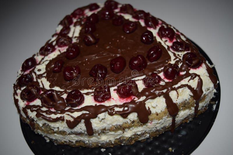 Hjärtaformkaka Vallmokrämkaka med den vita toppning och körsbäret överst, produktfotografi för bakelser Choklad socker arkivfoto