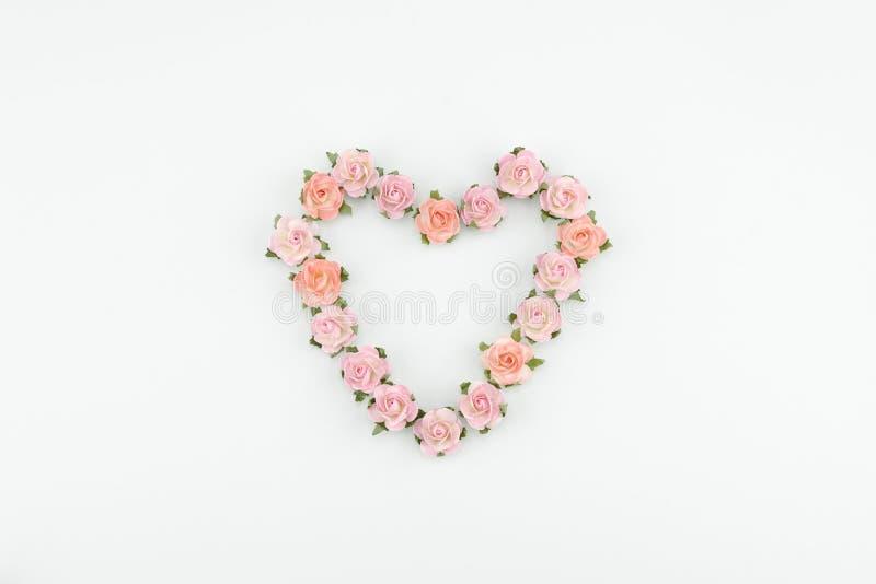Hjärtaformkrans som göras från rosa och orange pappers- blommor arkivbild