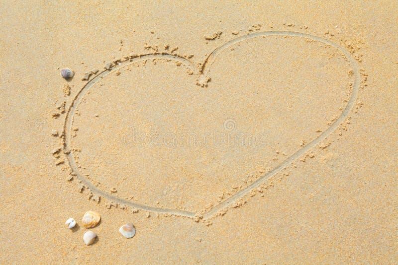 Hjärtaformteckning på bakgrund för sandstrandtextur kopiera avstånd royaltyfri fotografi