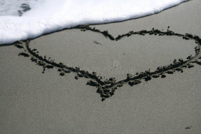 Hjärtaformteckning på sanden royaltyfria foton
