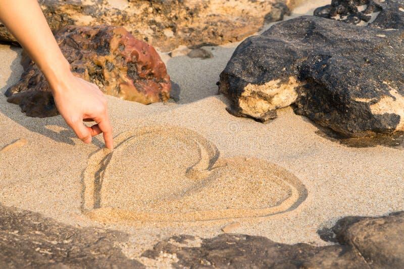 Hjärtaformteckningen på den vita sandnaturen mellan vagga, förälskelse vaggar in Sommartur royaltyfri bild