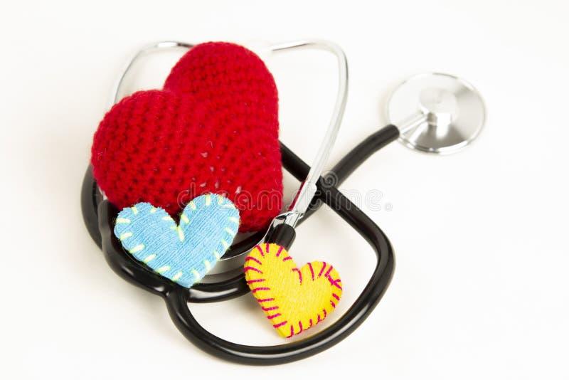 Hjärtahälsa och förhindrandebegrepp Stetoskop och röd hjärta av virkning på vit isolerad bakgrund med utrymme för text royaltyfri bild