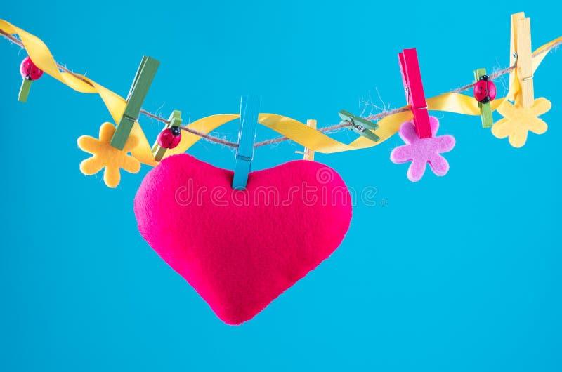 Hjärtakort som klämmas fast på klädstreck Kopieringsutrymme för wordings Klämt fast med blommaben Blått orange bakgrund högt arkivfoto