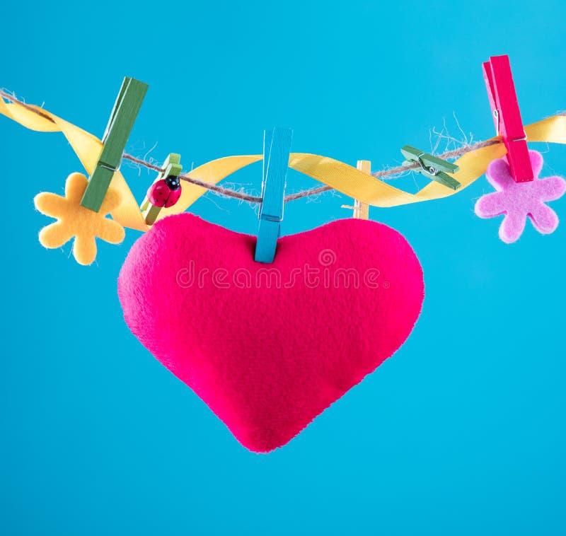 Hjärtakort som klämmas fast på klädstreck Kopieringsutrymme för wordings Klämt fast med blommaben Blått orange bakgrund högt royaltyfria foton