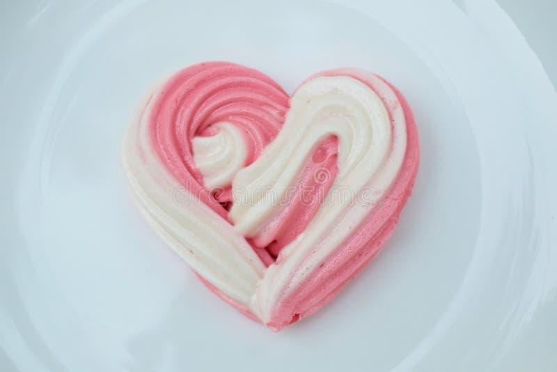 Hjärtamarängar planlägger vid socker i hjärtaform på plattan för hemlagad förälskelse i valentins daggarnering arkivfoton