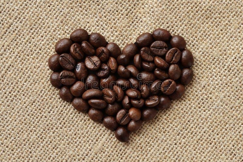 HjärtaShape som skapas från nya kaffebönor - linnebakgrund arkivbild
