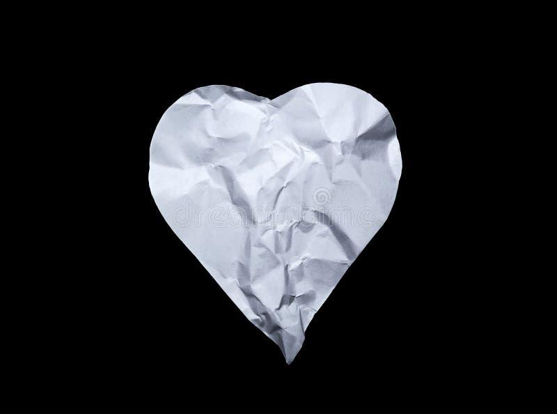 Hjärtasymbol från gammalt skrynkligt papper som isoleras på en svart bakgrund arkivbilder
