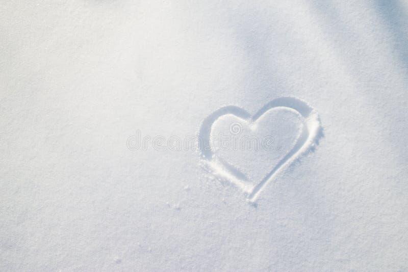 Hjärtasymbol som dras på den vita snön på en frostig solig vinter D royaltyfri fotografi