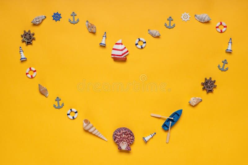 Hjärtasymbol som göras av dekorativa objekt, miniatyrleksaker: snäckskal fartyg, skyttel, ankaren, styrninghjul, livboj idérikt arkivfoton