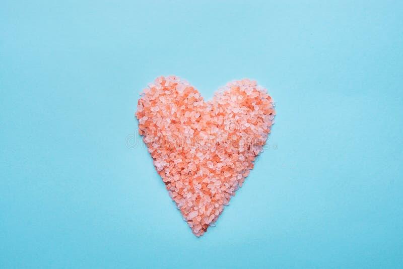 Hjärtasymbol som göras från salta rosa Himalaya på ljus - blå bakgrund Begrepp för förälskelse för dag för Valentine Mother ` s r royaltyfria bilder