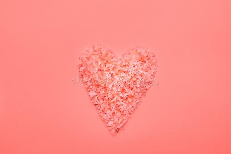 Hjärtasymbolet i moderiktig bosatt korallfärg gjorde från rosa Himalaya saltar kristaller på monokrom bakgrund valentin royaltyfria foton