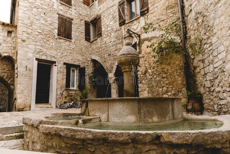 hjärtförmak av forntida byggnader på den gamla staden med den härliga springbrunnen, Peille, Frankrike royaltyfri bild