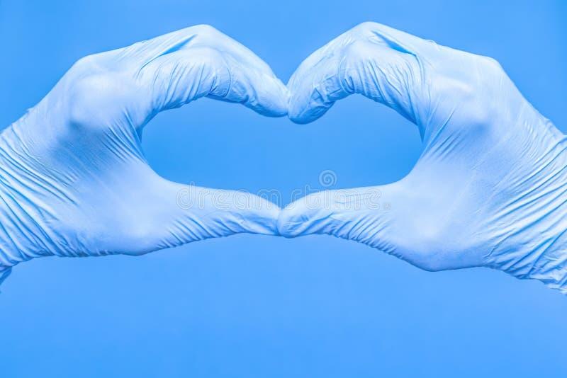 Hjärtform bestående av händer i handskar Hjärta tillverkad av handskar på blå bakgrund Hjärtform tillverkad med arkivbild