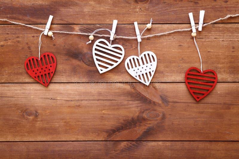 Hjärtor för för bakgrund för valentindag som romantiska dekorativa, röd och vit handgjord träleksak hänger på den bruna trätabell royaltyfria bilder