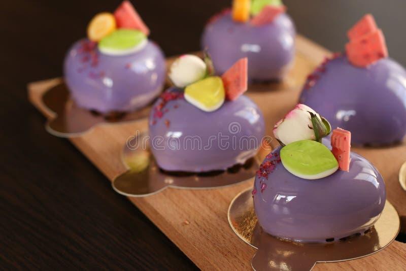 Hjärtor för hemlagade ljusa moussekakor 'med purpurfärgad spegelisläggning fotografering för bildbyråer