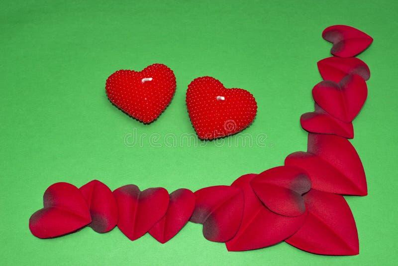 Hjärtor i rosa kronblad och stearinljus för dag för valentin` s arkivfoto