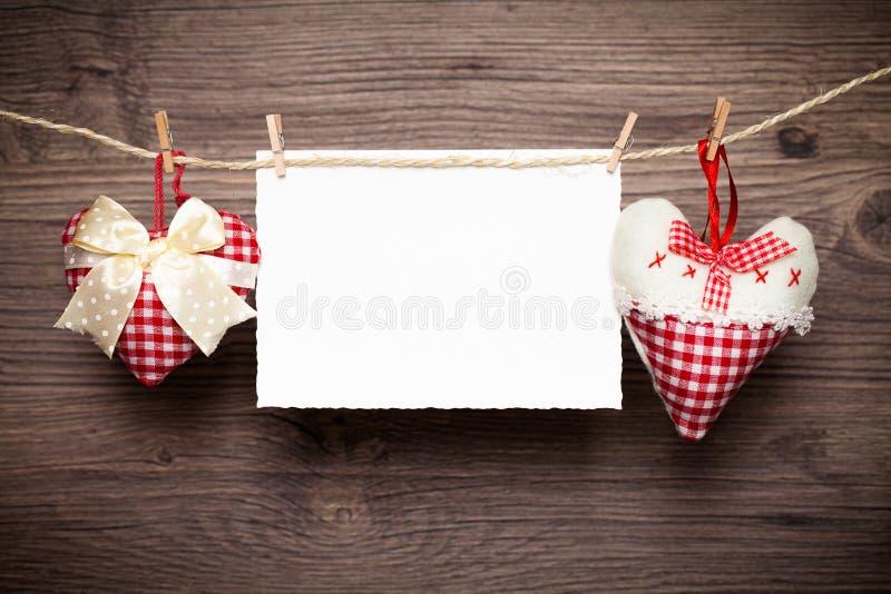 Hjärtor och ett tomt meddelandekort royaltyfri foto