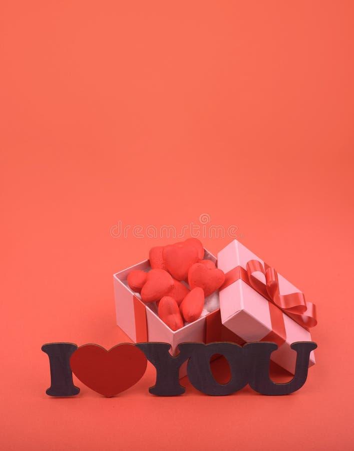 Hjärtor och gåvaask på en röd bakgrund utrymme för valentindagkopia royaltyfri fotografi