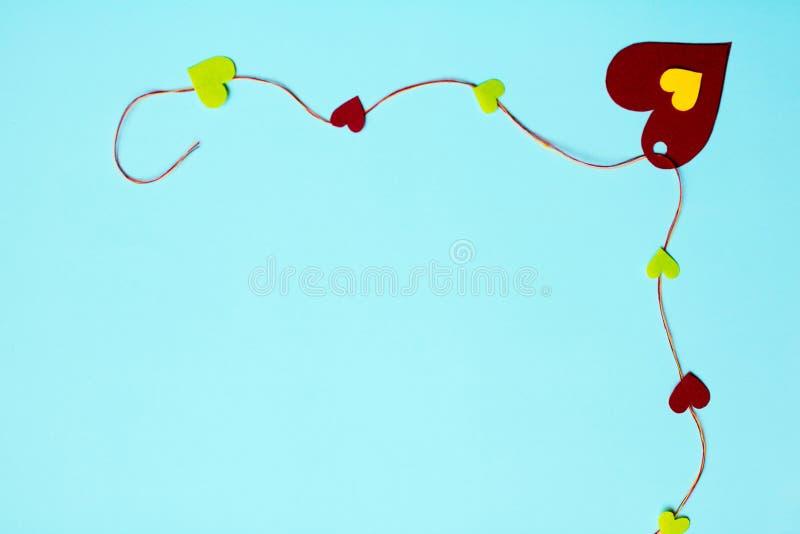 Hjärtor på en försiktig blå bakgrund, bunden färgrik tråd fotografering för bildbyråer