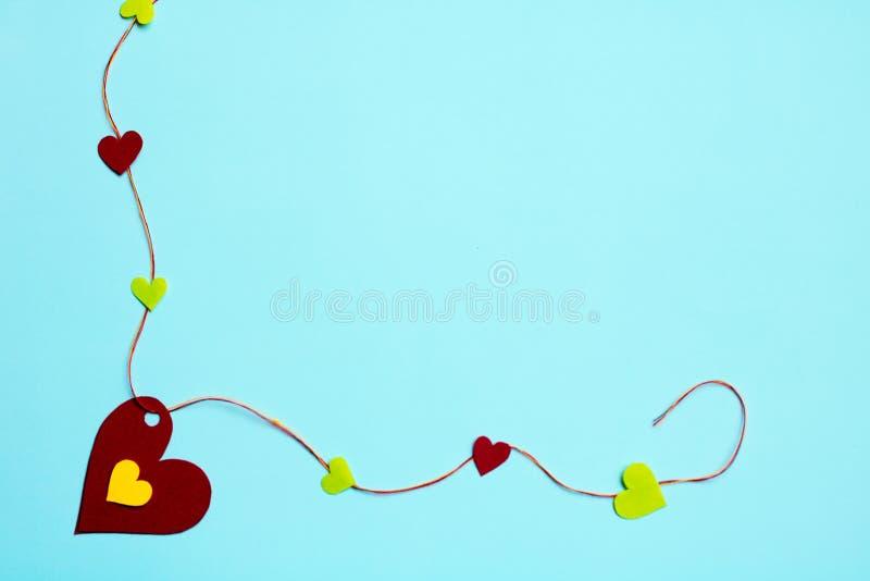 Hjärtor på en försiktig blå bakgrund, bunden färgrik tråd royaltyfri fotografi