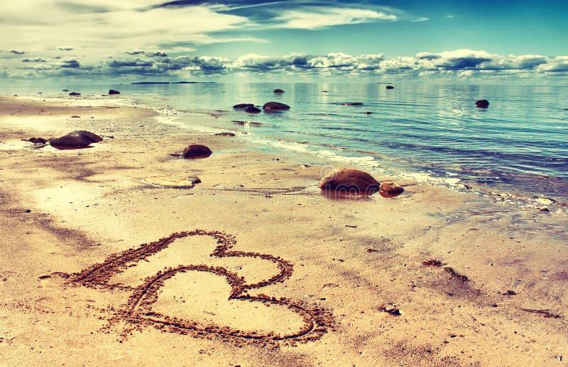 Hjärtor på sanden royaltyfri foto