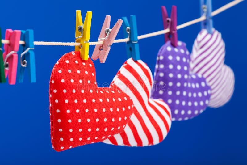 Hjärtor som hänger på en klädstreck med klädnypor royaltyfri foto