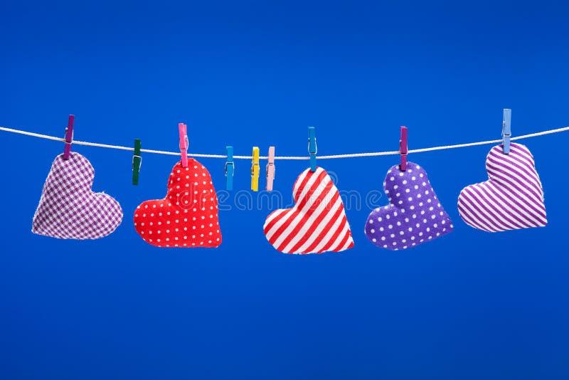 Hjärtor som hänger på en klädstreck med klädnypor, blåttbackgroun arkivbilder