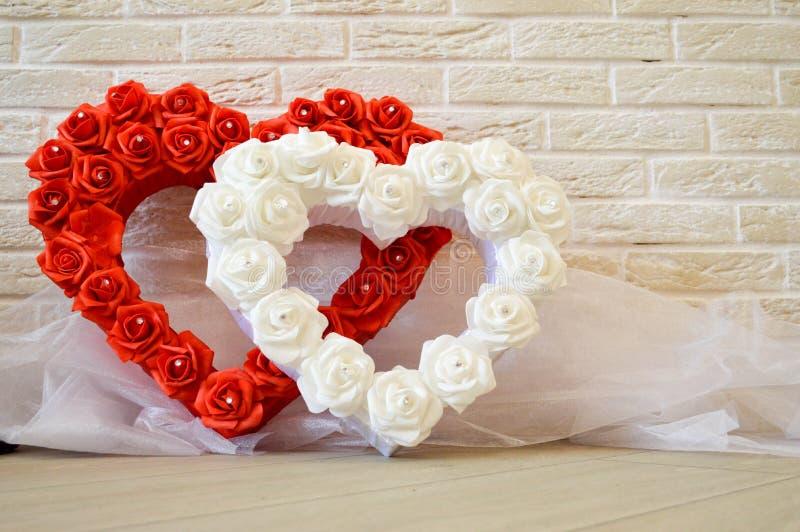 hjärtor två Röda och vita hjärtor med en modell av rosor royaltyfria foton