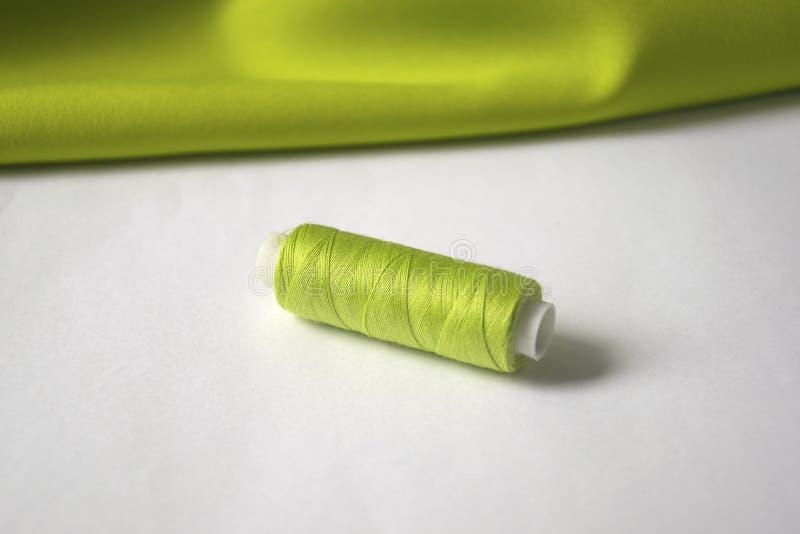 Hj?lpmedel f?r att sy och handarbete gröna trådar och grönt tyg royaltyfri foto