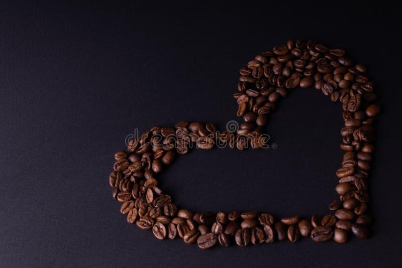 Hj?rta som fodras med kaffeb?nor arkivfoto